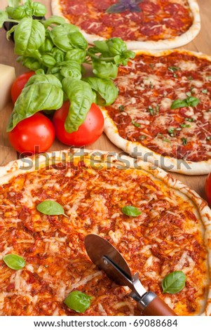 three different pizzas with basil, tomatoes and cheese on a wooden table - stock photo