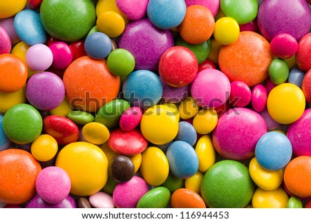 Three different sizes of colorful candies.Colorful background. - stock photo