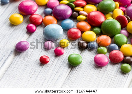 Three different sizes of colorful candies on wooden table. - stock photo