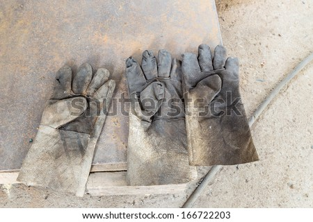 Three dirty leather gloves on floor - stock photo