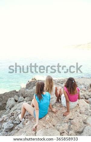 Three diverse friends, caucasian and african american teenager girls relaxing together on textured rocks contemplating the blue sea, outdoors nature. Healthy holiday travel lifestyle, beach exterior. - stock photo