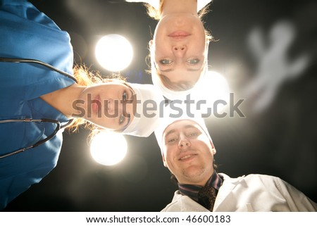 three doctor on operations with white lamp - stock photo