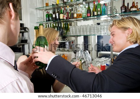Three drunk people at the bar, drinking champagne - stock photo