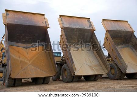 Three dump trucks from behind - stock photo