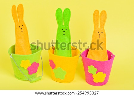 Three easter Bunnies in buckets on yellow paper background - stock photo