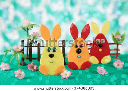 Three Easter bunny toy in the form of eggs on the lawn. - stock photo