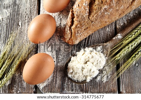 three eggs bread and flour on table  - stock photo