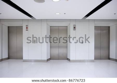 Three elevator doors in office building - stock photo