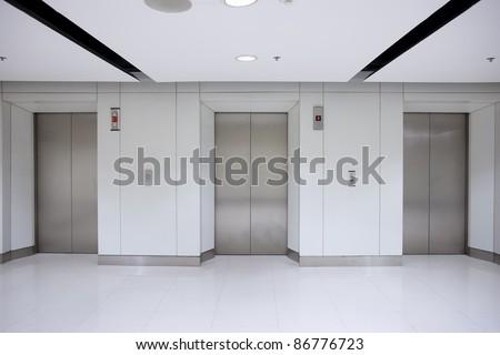 Three elevator doors in office building - stock photo