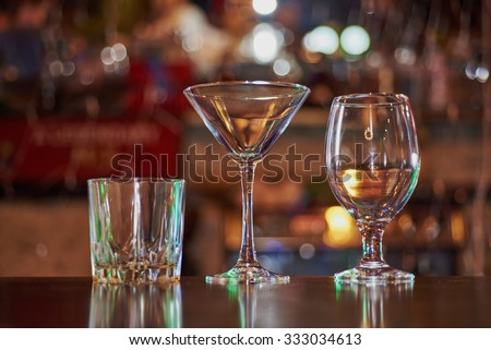 three empty glasses (martini, cocktail, whiskey) on the wooden bar on the background circular bokeh  - stock photo