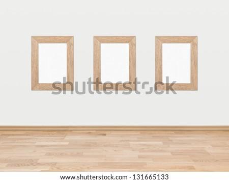 Three empty rectangular wooden frames displayed on a white wall above a hardwood wooden floor. - stock photo
