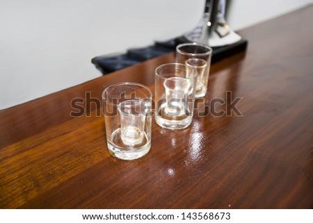 Three empty shot glasses on a bar - stock photo