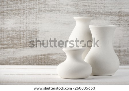 Three empty white unglazed ceramic vases on white wooden table against rustic wooden wall. - stock photo