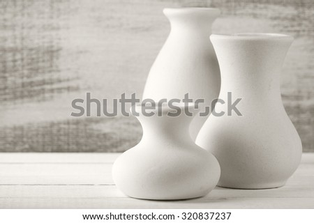 Three empty white unglazed ceramic vases on white wooden table against rustic wooden wall. Shallow DOF. - stock photo