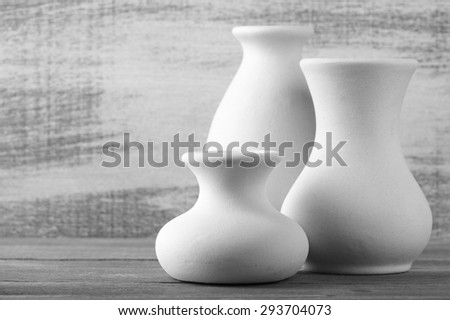 Three empty white unglazed ceramic vases on wooden table against rustic wooden wall. Black and white image. Shallow DOF, focus on front small vase. - stock photo