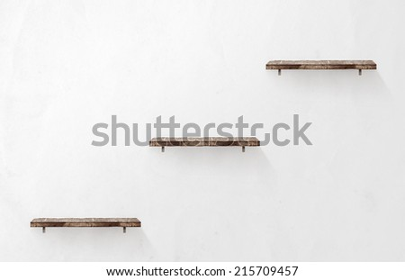 Three empty wooden shelves on the wall - stock photo