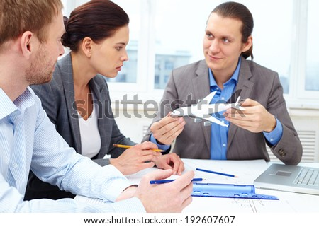 Three engineers discussing a small model of a plane while making its sketch - stock photo