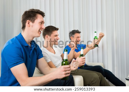 Three Excited Friends Sitting On Couch Holding Beer Bottles - stock photo