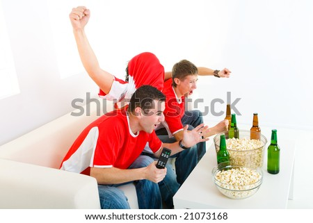 Three exciting men sitting on couch and watching sport on TV. - stock photo
