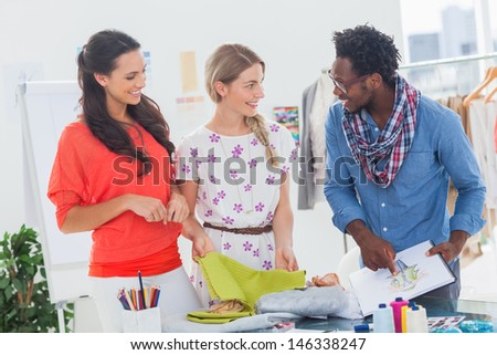 Three fashion designers looking at sketchpad in a bright creative office - stock photo
