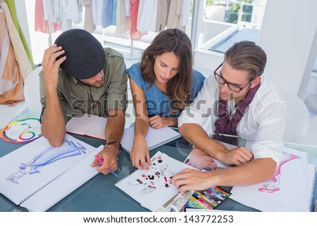 Three fashion designers working together in a bright office - stock photo