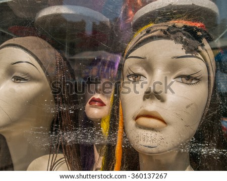 Three female caucasian mannequin heads wearing scarves with very serious expressions in a scratched up store front window in Manhattan, New York City, USA. - stock photo