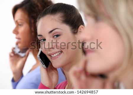Three female friends on mobile telephones - stock photo