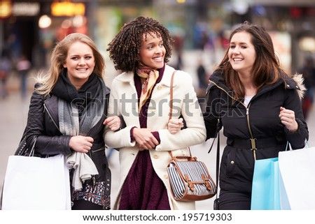 Three Female Friends Shopping Outdoors Together - stock photo