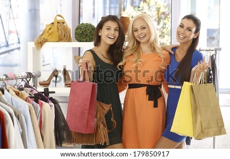 Three female friends standing at clothes store with shopping bags, smiling happy at camera. - stock photo