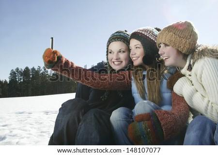 Three female friends taking self portrait in snow - stock photo