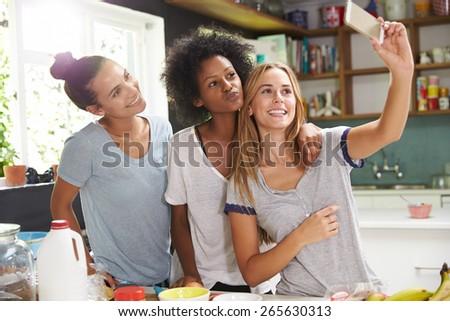Three Female Friends Taking Selfie Whilst Making Breakfast - stock photo