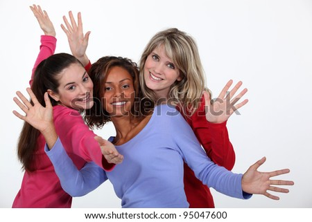 Three female friends waving - stock photo