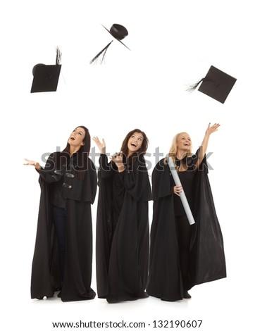 Three female graduates in academic dress throwing in the air square academic cap smiling happy. - stock photo