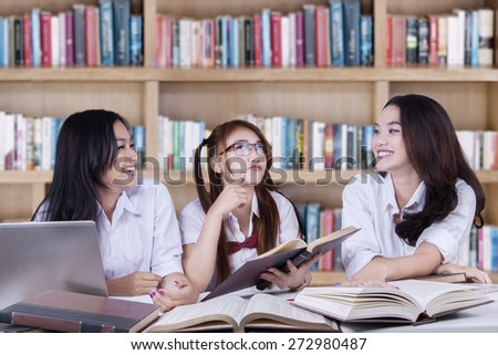 Three female high school student sitting in the library while studying and laughing together - stock photo