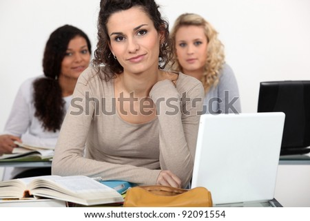 Three female students studying with their laptops. - stock photo