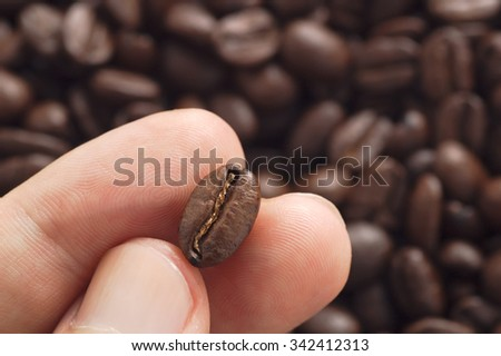 Three fingers showing roasted coffee bean with blurred other beans scattered behind. Shallow depth of field focused on coffee bean. Concept of individual approach to quality control. - stock photo