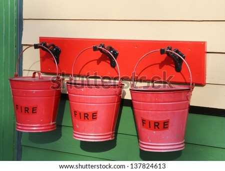 Three fire buckets hanging on a wall. - stock photo