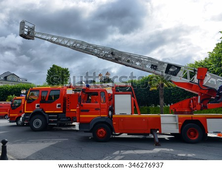 three fire trucks parked in the bay with all of the fire fighting equipment and gear ready to go - stock photo
