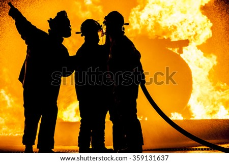 Three firefighters fighting a fire - stock photo
