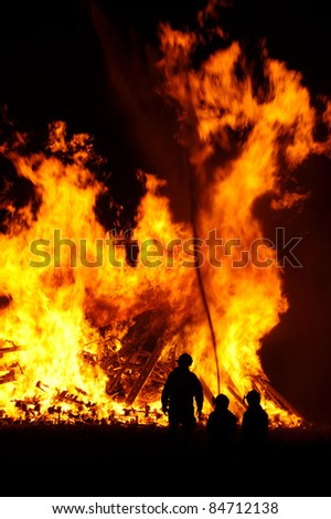 Three firefighters silhouetted against a massive blaze - stock photo