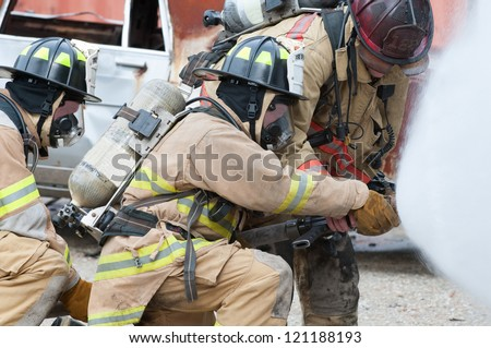 Three firemen extinguishing a car fire. - stock photo