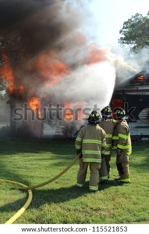 Three firemen work together to help put out blazing home fire by spraying it down with a high pressure water hose. - stock photo