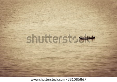 Three fisher men on a boat in the lake - stock photo
