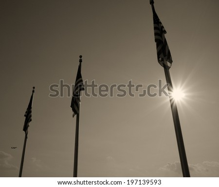 Three flags are limp in front of the sky and sun. - stock photo