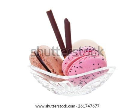 Three flavors of macaroon cookies in a small crystal bowl.  Shot on white background. - stock photo