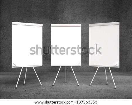 three flip chart on tripod and concrete room - stock photo