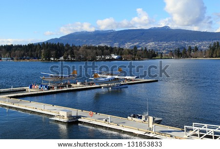 Three float planes docked in a harbour. - stock photo