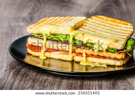 Three floor Panini toast with bacon, arugula, pepperoni salami and hollandaise sauce - stock photo