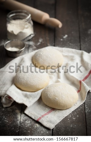 Three floured balls of uncooked homemade pizza dough on a kitchen towel on a rustic dark wooden table with flour and rolling pin. - stock photo
