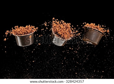 Three flying capsules full with instant coffee - stock photo
